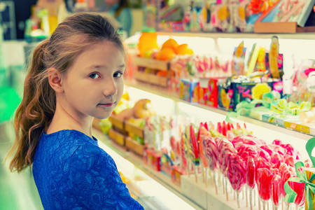 A girl in a candy store chooses multicolored candies and lollipops.
