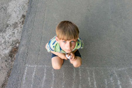 A poor and unhappy boy sits on the asphalt and asks for help while looking into the camera.