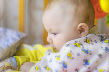 A newborn baby is lying in a crib and playing with toys, close-up.