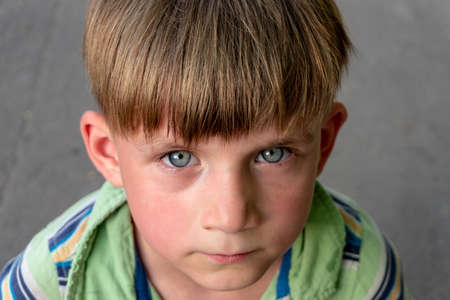 The poor and unhappy boy cries with tears in his eyes and asks for help while looking into the camera.