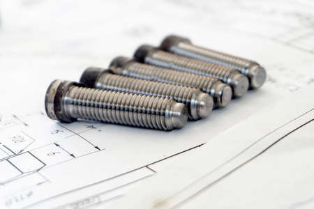 Bolts after turning with thread on the background of technical drawings.