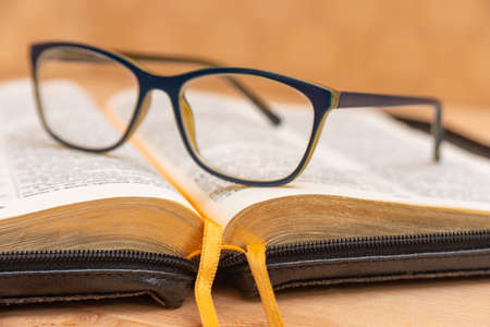 Glasses for sight lie on the Bible, the Bible in leather black cover with tabs lies on the table.