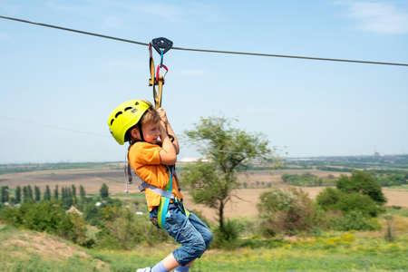 Een jongen gekleed in een beschermende helm en verzekering, gaat langs het touw, daalt af met een beschermende kabel. Stockfoto