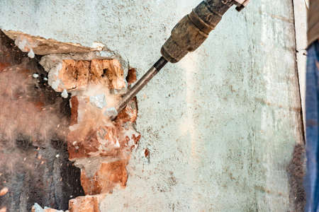 Disassembly of walls and openings with an electric jackhammer, close-up, dust hoarse from under the chisel.