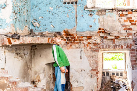 Orphaned children, poor child standing in a destroyed and abandoned building, staged photo.