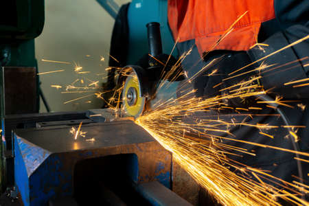 A worker saws a metal blank with a cutting wheel with a grinding machine, large sparks fly around. 版權商用圖片