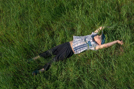 A happy and joyful boy is lying on the grass, a carefree childhood.