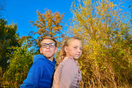A boy with glasses next to a girl in the fall in the park, a young friendship and affection. Banco de Imagens