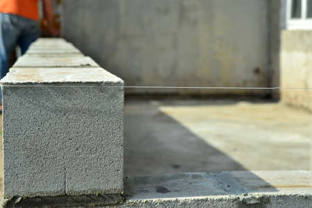 Laying gray cinder block on cement mortar, building walls and buildings.