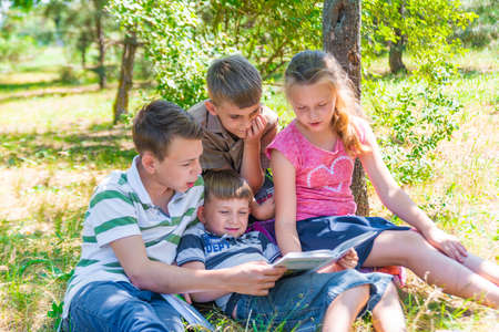 Children read a book in the park, brothers and sisters friends are studying science.