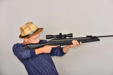 A boy with an air rifle looks into an optical sight.