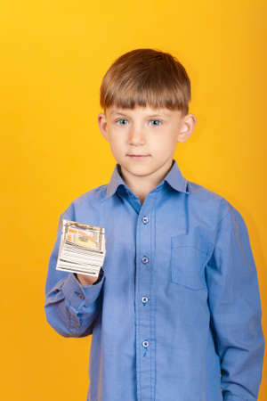 The boy holds a pack of banknotes, dollars in the hand of a child on a yellow background.