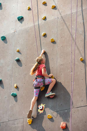 The girl on the tower of climbers conquers the peaks in an extreme park.