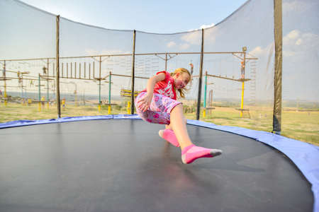 A girl in red clothes jumping on a trampoline in an amusement park.