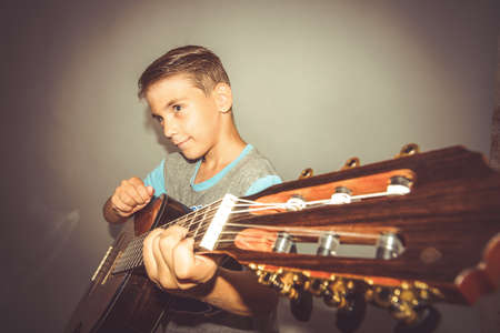 A boy plays the guitar on a gray background in the studio, wide-angle close-up photo.