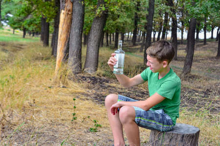 A teenager with alcohol in the park, the boy is sleeping after intoxication. Problems of child alcoholism. Stockfoto