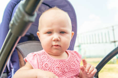 A child in a pushchair outside in the park, a little girl looks into the camera. Stockfoto