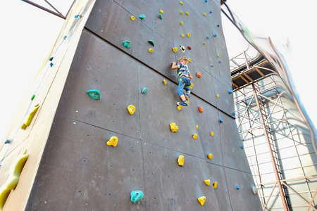 The boy on the towers of rock climbers, overcomes obstacles in an extreme park. Stockfoto