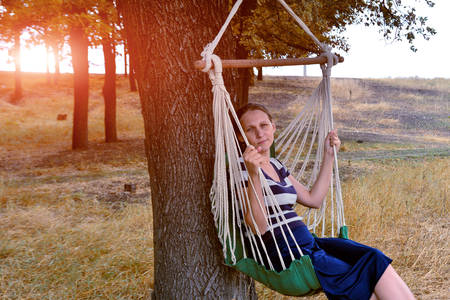 The girl in the park is resting and sitting on a hammock, against the background of the evening sun and looking into the distance. Stockfoto