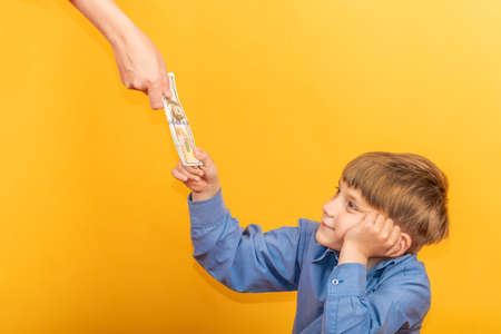 The boy in the blue shirt stretches out his hand and takes the dollars. Stockfoto