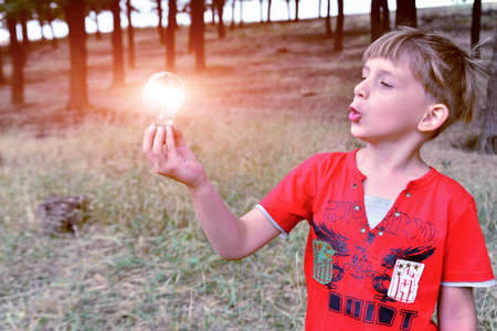 The boy holds an incandescent light bulb, which burns in his hand and looks at her with surprise and admiration.