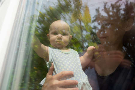 The child looks out of the window, the little girl looks out the window, and her mother holds her. Stockfoto