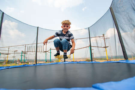 The boy jumps on a trampoline in an amusement park, performing various stunts. Stockfoto