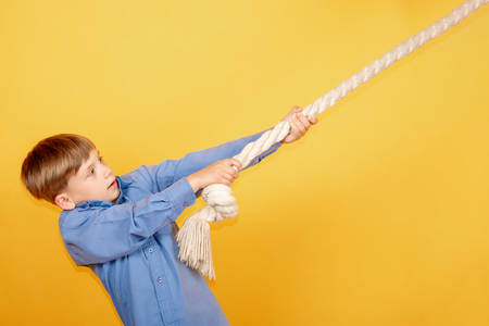 The boy stretches on a rope on a yellow background, the concept of achieving success. Stockfoto