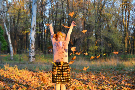 The girl is having fun and throwing leaves up in the autumn park.