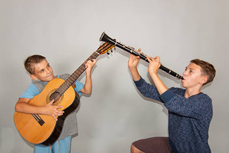 The boy plays the guitar and clarinet in different poses, posing in the studio.