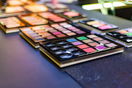 Exhibition of cosmetics in a boutique, eyeshadow on sale in a store. Colorful and gorgeous colors for professional makeup.