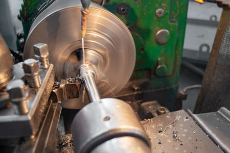 The manufacture of metal parts on a lathe, water-cooled. Stok Fotoğraf