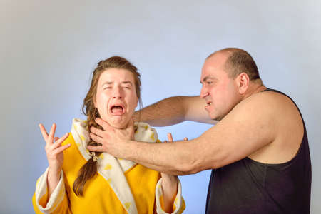 Aggressive husband abuses his power and beats his wife. Imagens