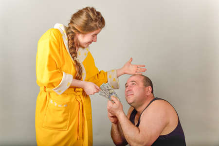 A wife beats her husband and takes money from him, the concept of social problems in families.