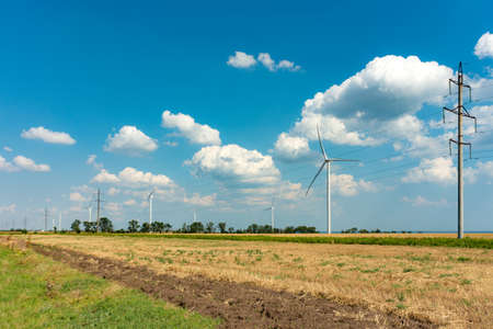 Wind generators with turbine engines and large blades. Electricity air generators are placed in the field. Stock Photo