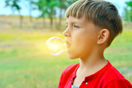 A light bulb glows in a person, a child holds a lighting device with his mouth. Foto de archivo