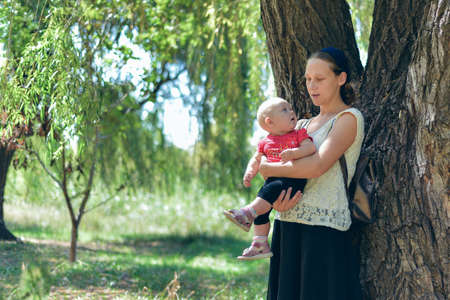 A woman with a small child is standing in a forest near a large tree. Stock Photo