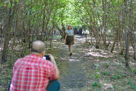 A man photographs a girl walking through the forest. 免版税图像
