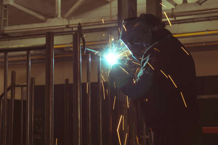 The welder makes the metalwork, connecting by welding, sparks fly along the sides.