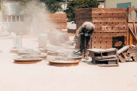 Sandblasting at an industrial plant, a worker knocks down oxide and dirty rust with sand under air pressure from a hose.