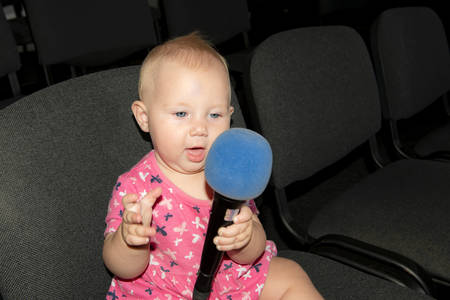 A little girl sits on a chair in the hall with a microphone in her hands.