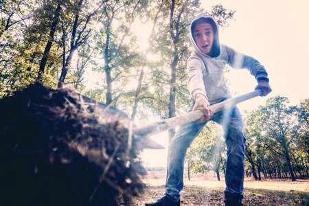 A man buries the ground with a shovel and throws it from above, a view from inside from below. Stock Photo