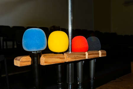 Four multi-colored microphones on a stand in an empty room with chairs without people. 스톡 콘텐츠