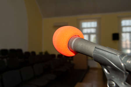 A microphone on a stand in an empty room with chairs without people.