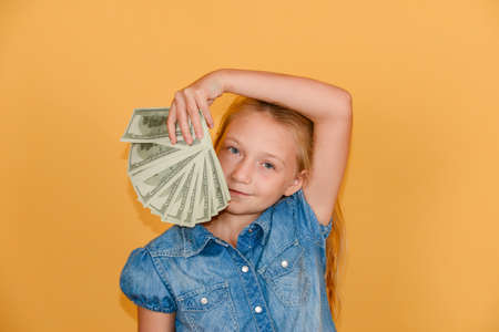 Happy and joyful girl holds dollars in her hands.