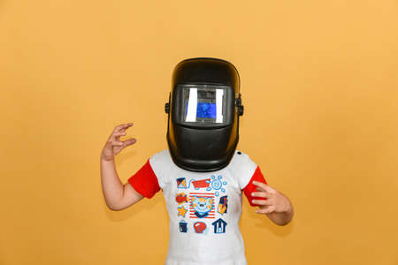 A boy in a welding mask waves his hands in different directions, on a yellow background.