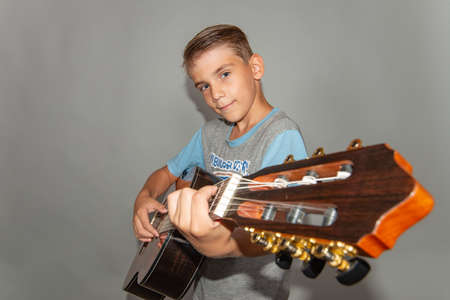 Boy with a guitar on a gray background in the studio, wide angle photo.
