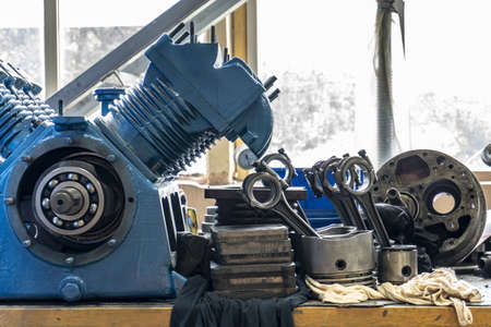 The connecting rod, piston and cylinder block in a disassembled condition in a car workshop.