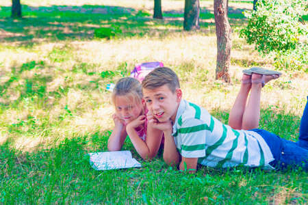 Boy with a girl doing homework on the grass in the park. 写真素材