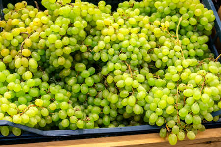 Fragrant and juicy grapes on the counter and in a wooden container in the store.